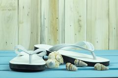 White flip flops with shellfishs on the blue wooden table. stock photography