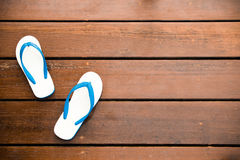 White Flipflops on a wood background. Vintage style royalty free stock images