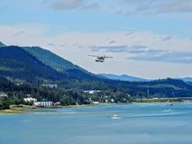 White Float Pontoon Seaplane Taking off from Juneau Harbor royalty free stock photos