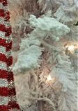 Holiday White Flocked Tree Branches with Red Striped Scarf. White flocked Christmas tree branches with white lights and red-striped sparkly scarf on left border Royalty Free Stock Photo