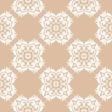 White floral ornament on beige background. Seamless pattern. White floral design on beige background. Seamless pattern for textile and wallpapers Royalty Free Stock Photo