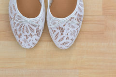 White floral lace ballet flat slip on shoes on wooden background. Top partial view of popular white floral lace ballet flat slip on shoes on wooden background stock photo