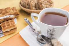 White with a floral pattern mug with tea, a spoon and lump brown sugar lie on a white square saucer. Next to the defocus of Viennese waffles and cookies on a Stock Images