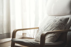 White Floral Throw Pillow in Brown Wooden Armchair Stock Images