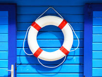 White flotation ring on the blue wall. Near boat rental stock images