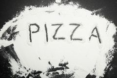 White flour on a black table, inscription pizza.  stock images