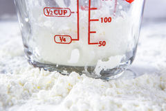 White flour and measuring cup on table. Royalty Free Stock Image