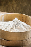 White flour on a sieve. For bread and bakery products on brown background Stock Photos
