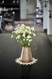 White flower in an antique metal jug Royalty Free Stock Image