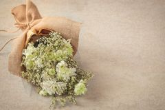 White flower bouquet in craft sack on old background Stock Images