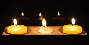A white flower candle in centre piece. Two yellow candles with a white flower in the centre Stock Images