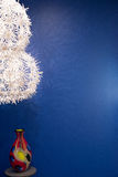 White flower lights with colored vase on blue wall Royalty Free Stock Photography