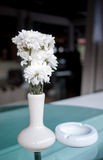White flower vase decorate on table. White flower vase and cigarette tray decorate on the glassy table top Stock Image