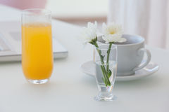 White flower in a vase with coffee and orange juice on table Stock Photography