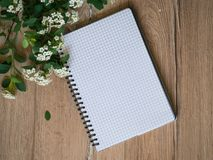 White flowers and blank notebook on wooden table, top view, flatlay stock photo