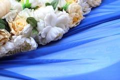 White flowers and blue drape stock image