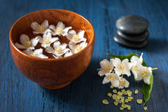 White flowers in a bowl, stones for massage and sea salt. Spa composition. Royalty Free Stock Photography