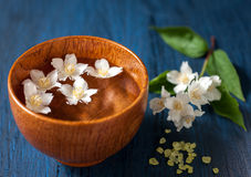 White flowers in a bowl of water and sea salt for spa Royalty Free Stock Images