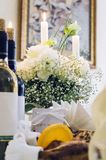 White flowers, candles and bottles of wine on a served table in a cafe stock photos