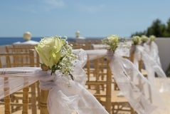 White flowers on chairs before a wedding ceremony. At a venue on the beach Royalty Free Stock Photo