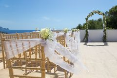 White flowers on chairs before a wedding ceremony. At a venue on the beach Stock Photo