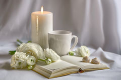 White flowers, cup, candle and a notebook on a white background Royalty Free Stock Image