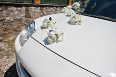 White flowers decoration on the hood of wedding car.  Royalty Free Stock Photos