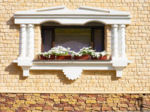 White flowers hangs on the window of a home in an ancient buildi Royalty Free Stock Photos