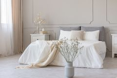 Free White Flowers In Vase In Elegant Grey Bedroom Interior With Simple Bedding Royalty Free Stock Photo - 147536145