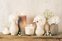 White flowers in neutral colored vases and candles. White flowers in neutral colored vases and burned candles on rustic wooden shelf against shabby white wall stock images
