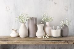 White flowers in neutral colored vases and candles. On rustic wooden shelf against shabby white wall. Home decor royalty free stock photo