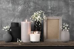 Neutral colored home decor. White flowers in neutral colored vases, frame and burned candles on distressed wooden shelf against rough plaster grey wall. Home royalty free stock photography