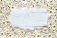 White flowers rose frame on white table. Frame of white rose flowers on white wooden table, top view Stock Images