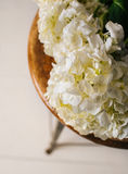 White Flowers on Stool. Pretty white flowers on an antique stool in front of a white wooden background Royalty Free Stock Photography