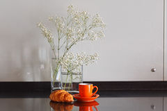 White flowers on a table in glass transparent vases with cup of royalty free stock images