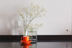 White flowers on a table in glass transparent vases with cup of royalty free stock photo