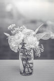 White flowers in a vase on the coffee table with a black and white stock photography