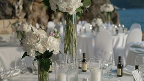 White flowers in vase are set on tables to a celebration by sea. Fine buds in long vessels decorate banquet furniture on embankment in summer weather stock video footage