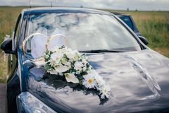 White flowers and wedding rings on the hood of the black car stock photos
