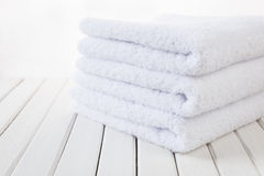 White fluffy bath towels. Stack of three white fluffy bath towels on the background of white boards Stock Photo