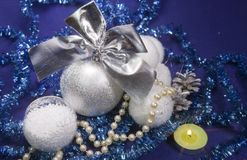 White fluffy beautiful New Year`s balls, brilliant tinsel and candle on a blue background - New Year`s composition, a card.  Royalty Free Stock Image