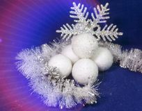 White fluffy beautiful New Year`s balls, brilliant tinsel and snowflake on a blue background - New Year`s composition, a card.  Stock Photography