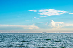 White fluffy clouds blue sky above a surface of the sea and boat Stock Images