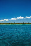 White fluffy clouds blue sky above a surface of the sea Stock Photography