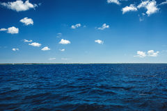 White fluffy clouds blue sky above a surface of the sea Royalty Free Stock Photography