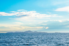 White fluffy clouds blue sky above a surface of the sea Royalty Free Stock Photo