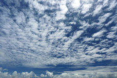 White, fluffy altocumulus clouds in the blue sky. Stock Images