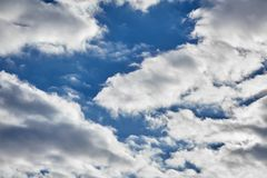 White fluffy clouds on a blue sky background. White fluffy soaring clouds on a blue sky background stock photos