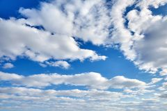White fluffy clouds on a blue sky background. White fluffy soaring clouds on a blue sky background royalty free stock image