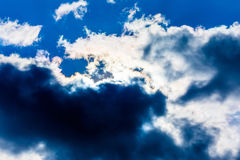 White fluffy clouds in the blue sky. Dramatic cloudscape with su Royalty Free Stock Images